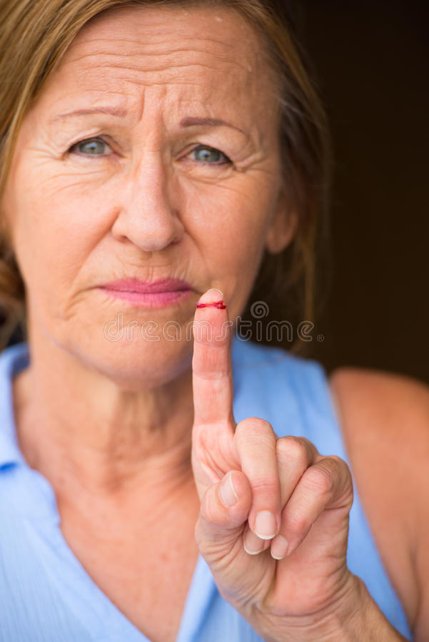 Mature Woman bloody cut finger wound. Portrait stressed mature woman in pain, hurt and suffering, close up of tissue on injured, cut bloody finger wound stock photography
