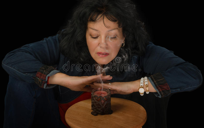 Mature woman blowing out the candle. Mature black haired woman in denim suit blowing out the candle on black background royalty free stock images