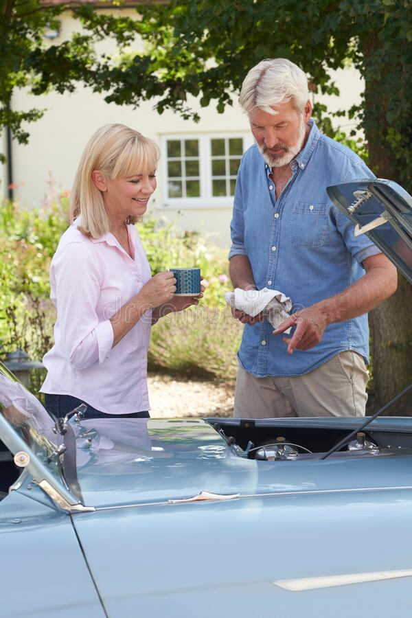 Mature Woman Bringing Hot Drink To Man Restoring Classic Sports Car Working On Engine Under Hood stock photography
