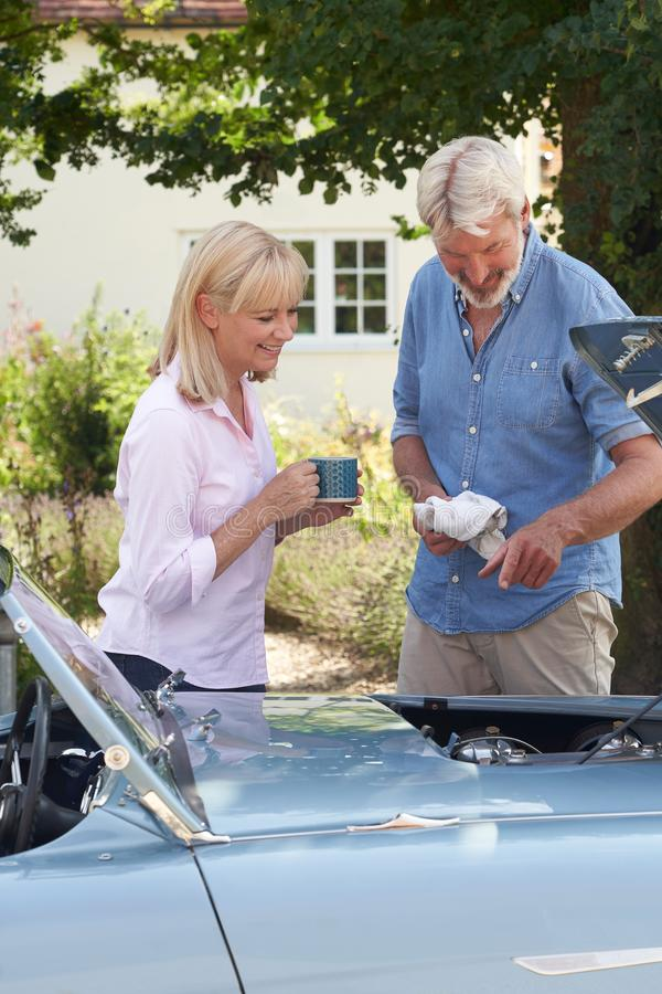 Mature Woman Bringing Hot Drink To Man Restoring Classic Sports Car Working On Engine Under Hood stock photos