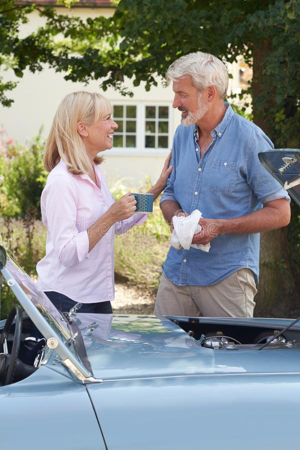Free Mature Woman Bringing Hot Drink To Man Restoring Classic Sports Car Working On Engine Under Hood Stock Image - 160005521