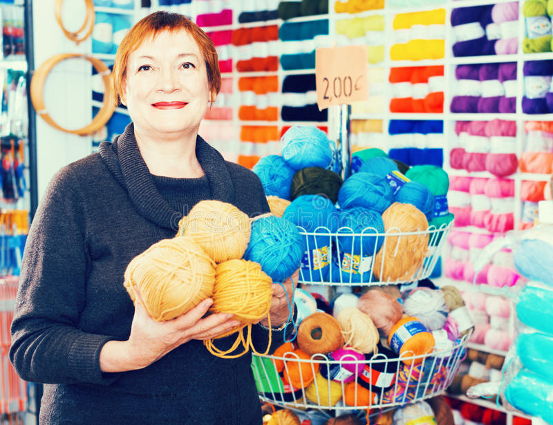 Mature woman buying yarn for their hobby on special offers. Cheerful positive smiling mature woman buying colorful yarn for their hobby on special offers stock photo