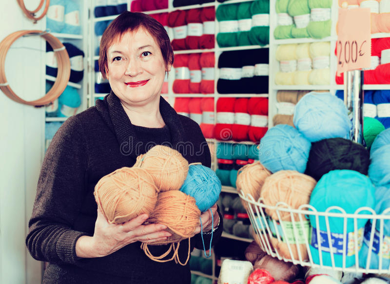 Mature woman buying yarn for their hobby on special offers. Glad positive smiling mature woman buying colorful yarn for their hobby on special offers stock images