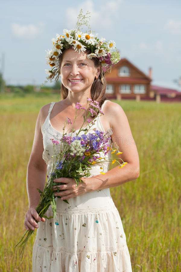 Mature woman in camomile wreath. Outdoor portrait of mature woman in camomile wreath stock images