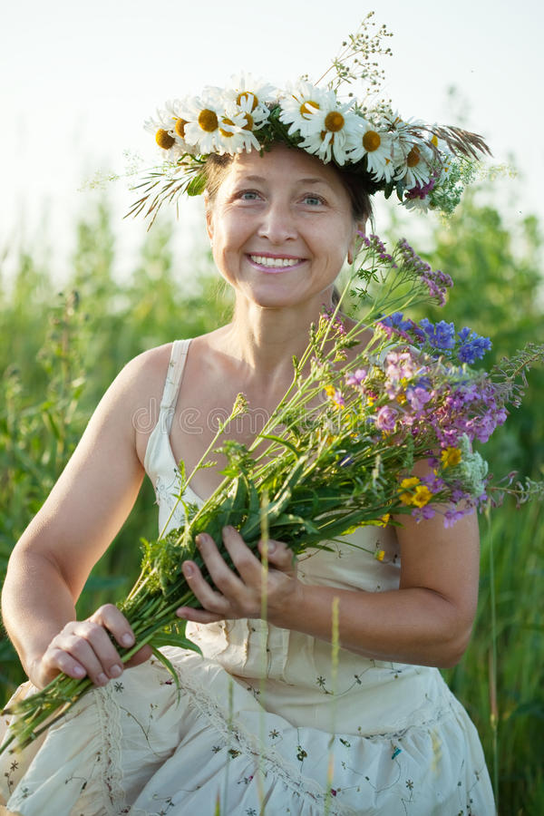 Mature woman in camomile wreath. Outdoor portrait of mature woman in camomile wreath stock photography