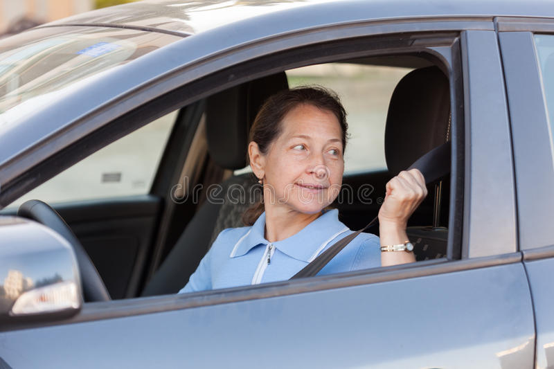 Mature woman in car. Mature woman driving black car royalty free stock photography