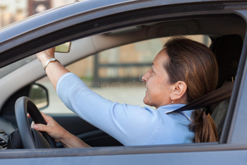 Mature woman in car. Mature woman driving black car royalty free stock photos