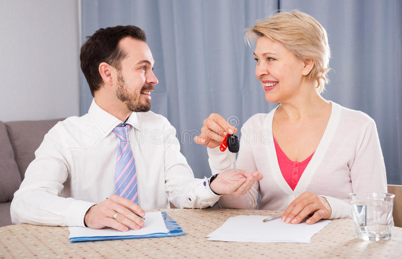 Mature woman and car lease manager. Woman and young manager sign contract car rent and hand over keys stock photos