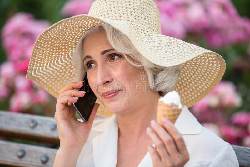 Mature woman with cell phone. Lady holds ice cream. Conversation with a friend. Need some time to talk stock photo