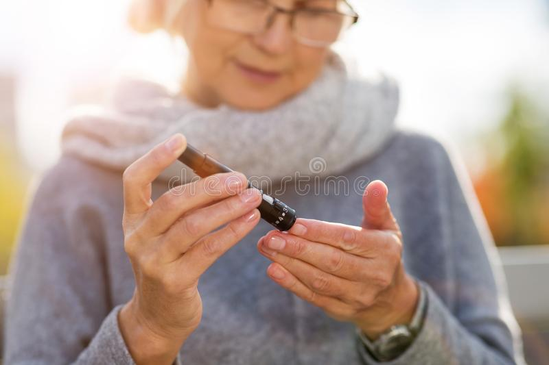 Mature Woman Checking Blood Sugar Level. With Glucometer stock image