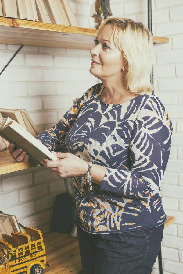Mature woman chooses a book stock photography