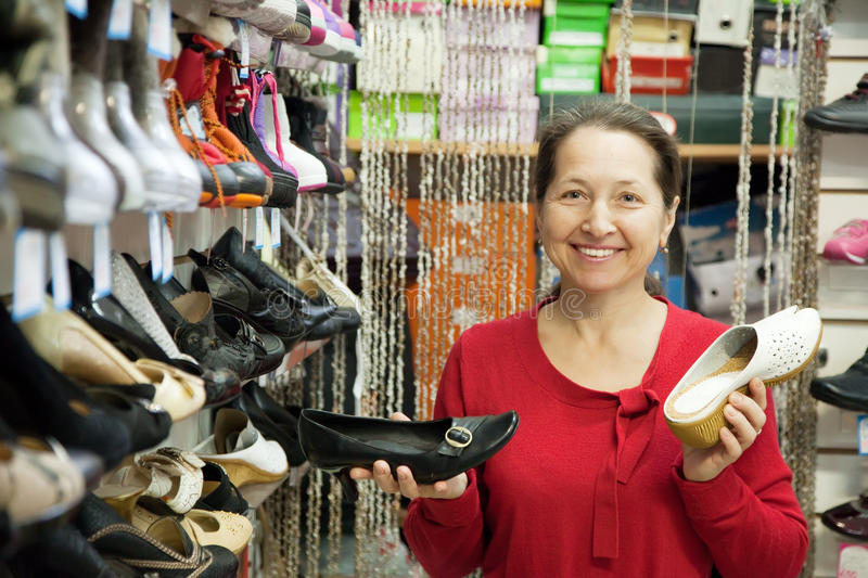 Mature woman chooses shoes royalty free stock photos