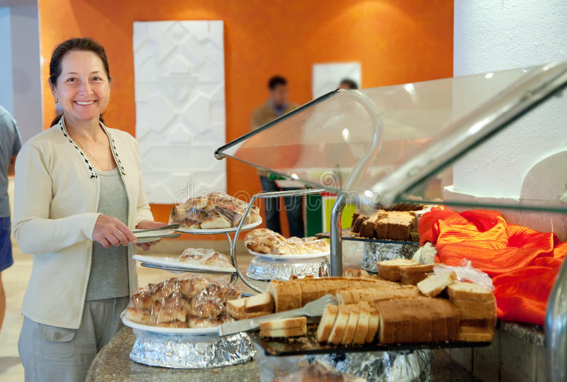 Mature Woman Chooses Sweet Pastry Royalty Free Stock Image