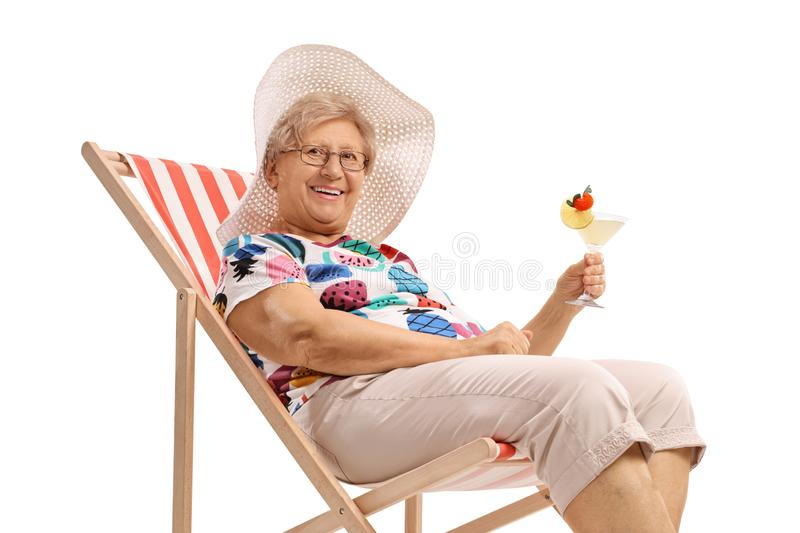 Mature woman with a cocktail sitting on a deck chair. Isolated on white background royalty free stock images