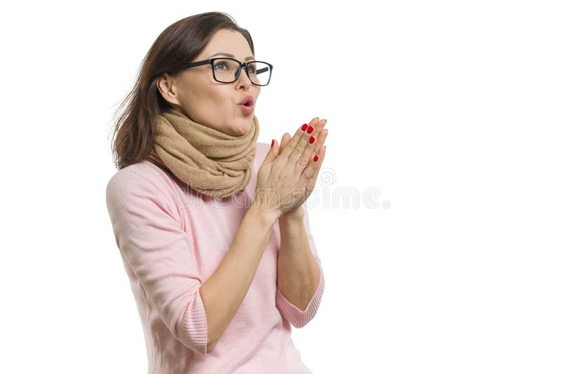Mature woman cold, wearing a scarf warming her hands with hot breath, white background isolated. stock image