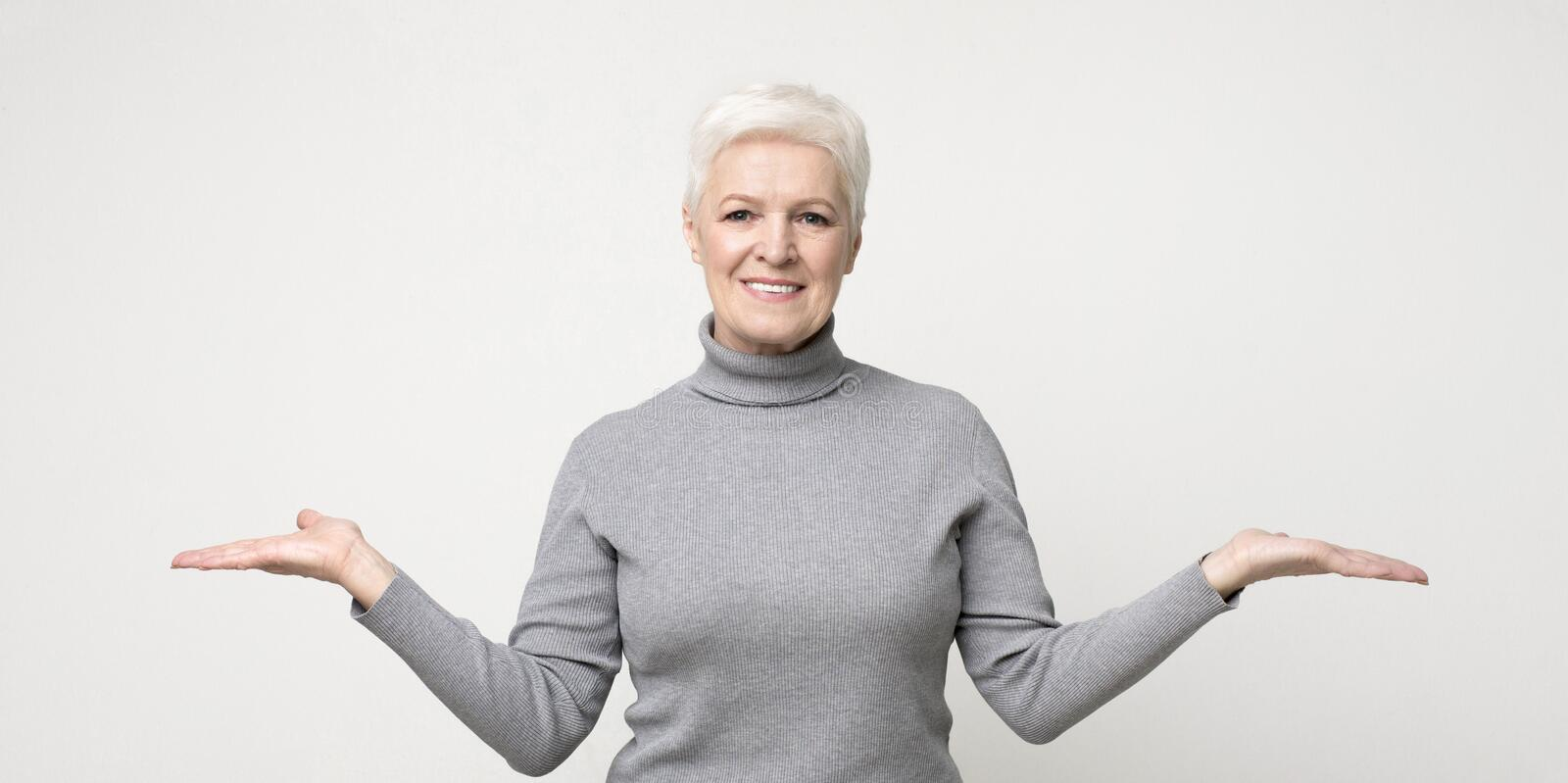 Mature woman comparing variants, making scales with her empty arms stock image