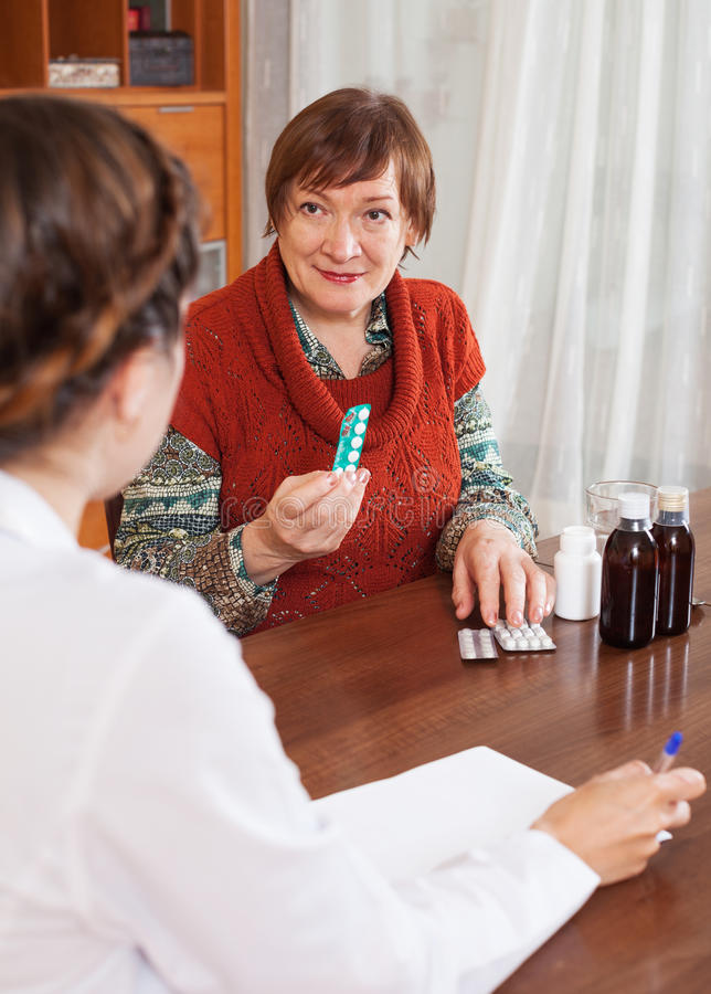 Mature woman complaining to doctor about symptoms royalty free stock photography