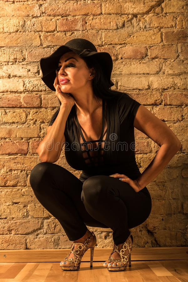 Mature woman crouching. A beautiful mature woman crouching in front of the wall in black clothes and hat stock image