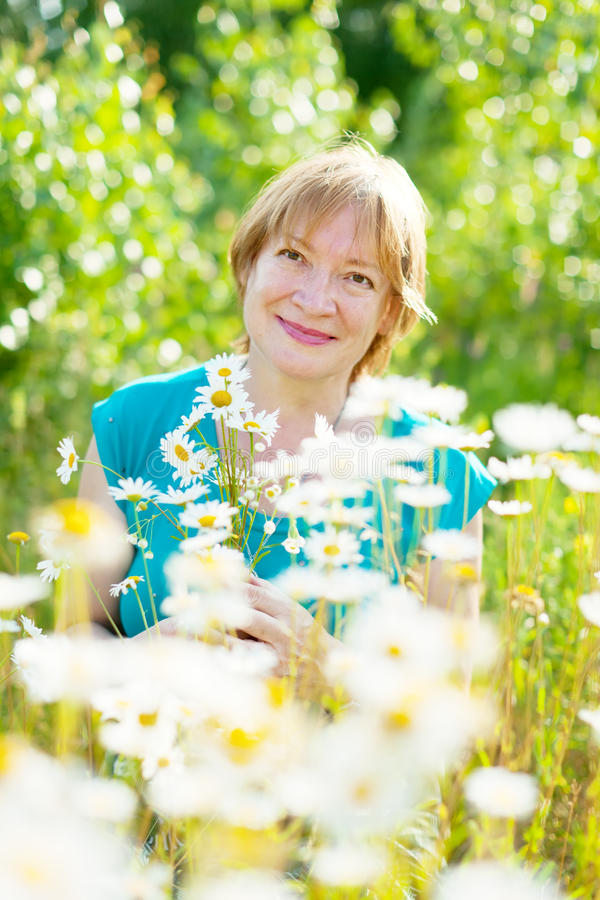 Mature woman daisy field stock photos