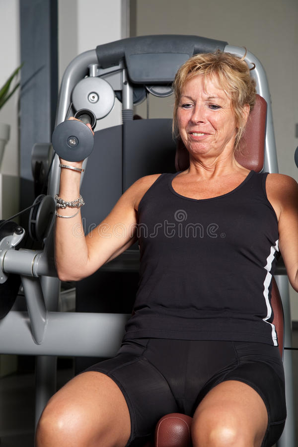 Mature woman doing exercise stock photography