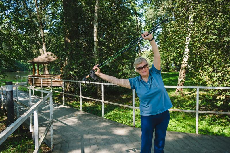 Mature woman doing exercises with Nordic walking poles in summer stock image