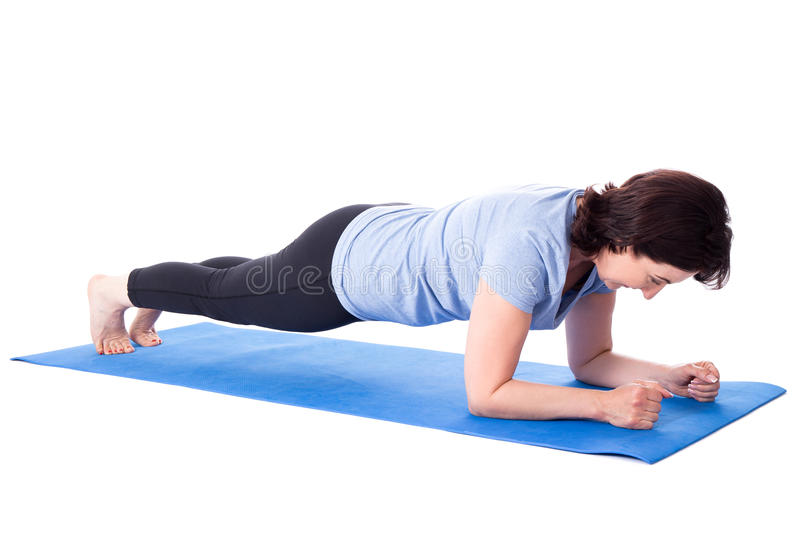 Mature woman doing exercises on yoga mat isolated on white royalty free stock photography