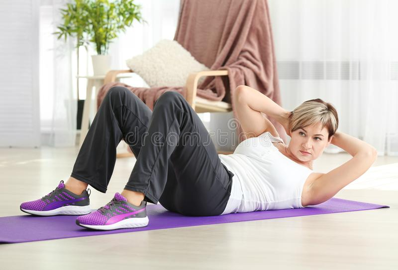Mature woman doing sit-ups at home. stock photo