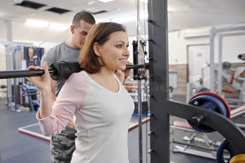 Mature woman doing sport exercises with personal trainer at gym. Male instructor assisting older woman royalty free stock photos
