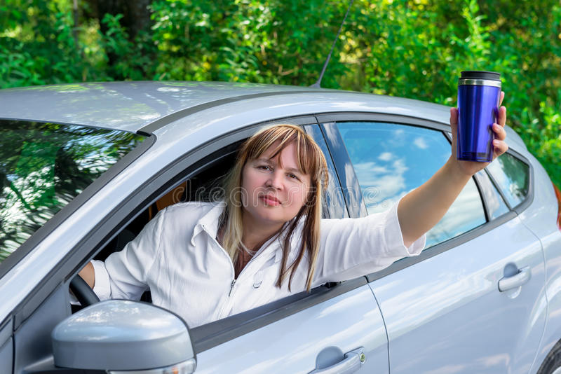 Mature woman with a drink looks out the car window stock photography