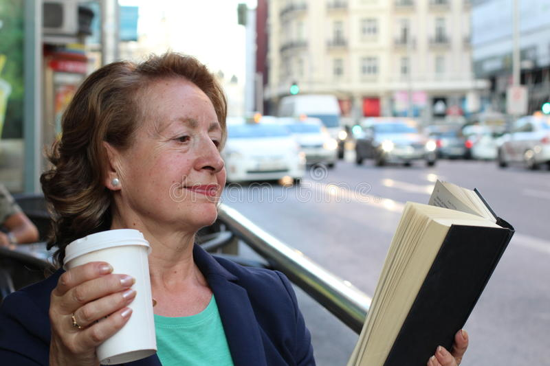 Mature woman drinking coffee and reading book sitting indoor in urban cafe. Cafe city lifestyle with traffic lights. In the background royalty free stock photos