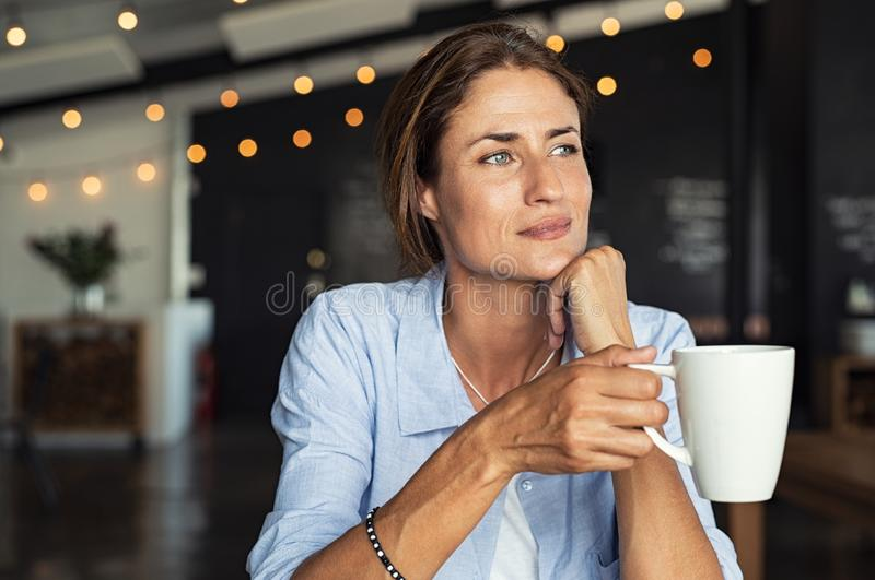 Mature woman drinking coffee stock photos