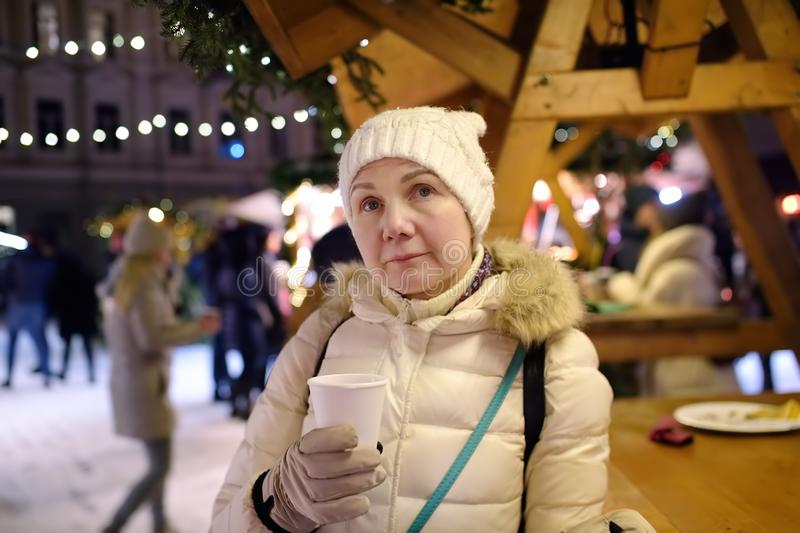 Mature woman is drinking hot mulled wine on Christmas market. Xmas holidays on famous fair in Tallinn, Estonia royalty free stock photo