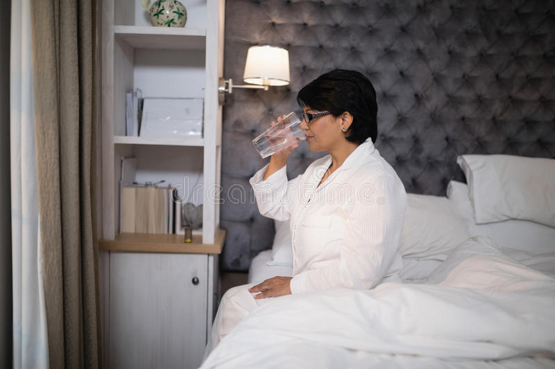 Mature woman drinking water while sitting on bed royalty free stock image