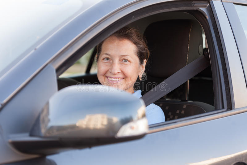 Mature woman driving black car. Portrait of senior woman in black car royalty free stock images