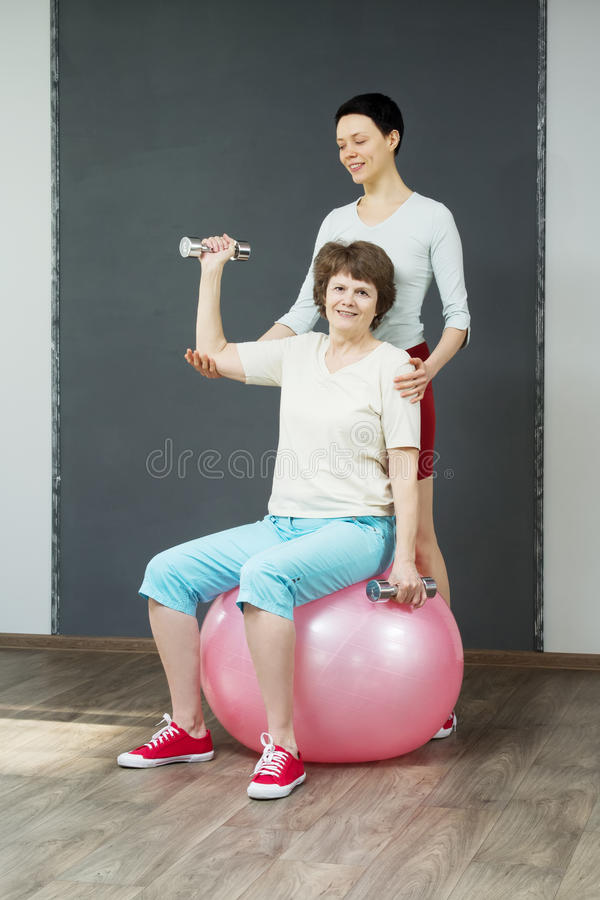 Mature woman with dumbbells and young coach royalty free stock image