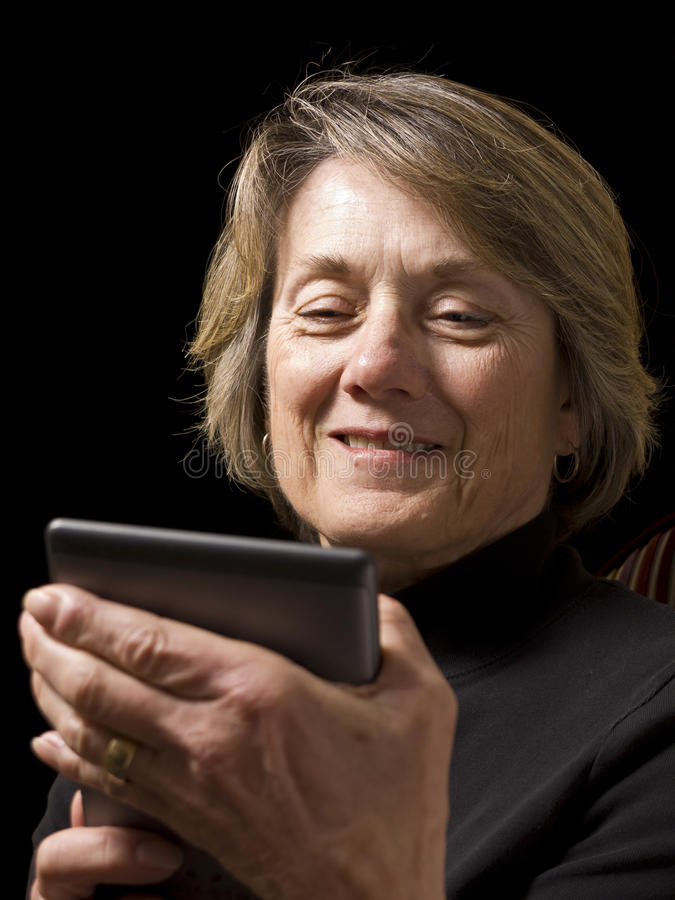Mature Woman With E-Reader. An adult mature senior woman reading a book on her electronic reader or e-reader device or an older women receiving a funny email stock images