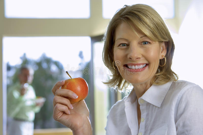 Mature woman eating apple at home, senior man in background, focus on woman, smiling, side view, portrait stock photos