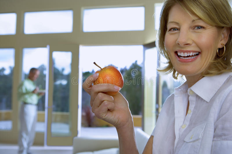 Mature woman eating apple at home, senior man in background, focus on woman, smiling, side view, portrait stock photography