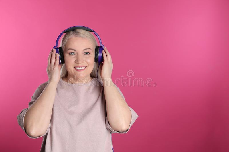 Mature woman enjoying music in headphones. Space for text. Mature woman enjoying music in headphones on color background. Space for text royalty free stock image