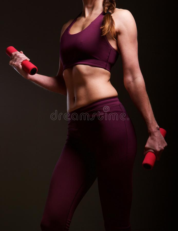 Mature woman exercising with aerobic weights. Mid section close up portrait of fit mature woman exercising with aerobic weights in studio royalty free stock photo