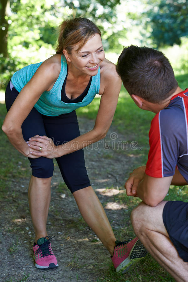Mature Woman Exercising With Personal Trainer In Park stock images
