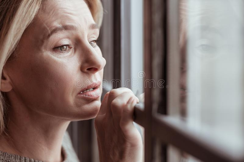 Mature woman with facial wrinkles feeling stressed and sad stock photography