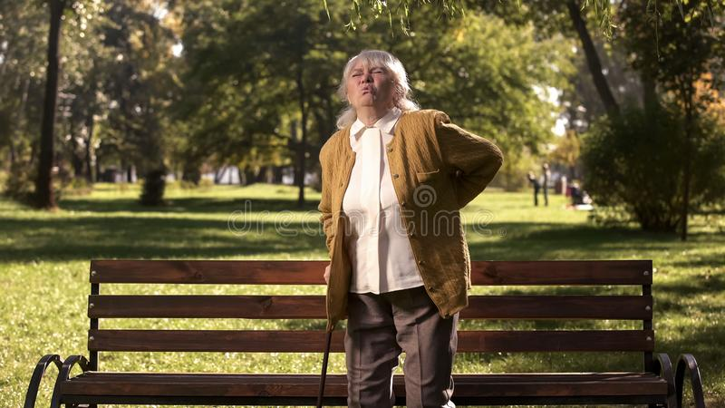 Mature woman feeling back pain standing up from park bench, health problems royalty free stock photo