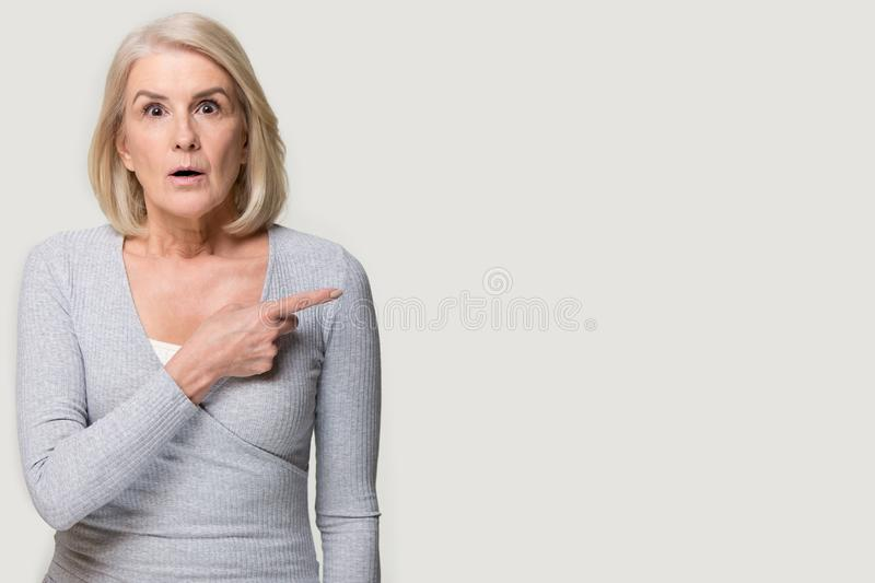 Mature woman feels astonished shocked pointing finger at copy space stock image