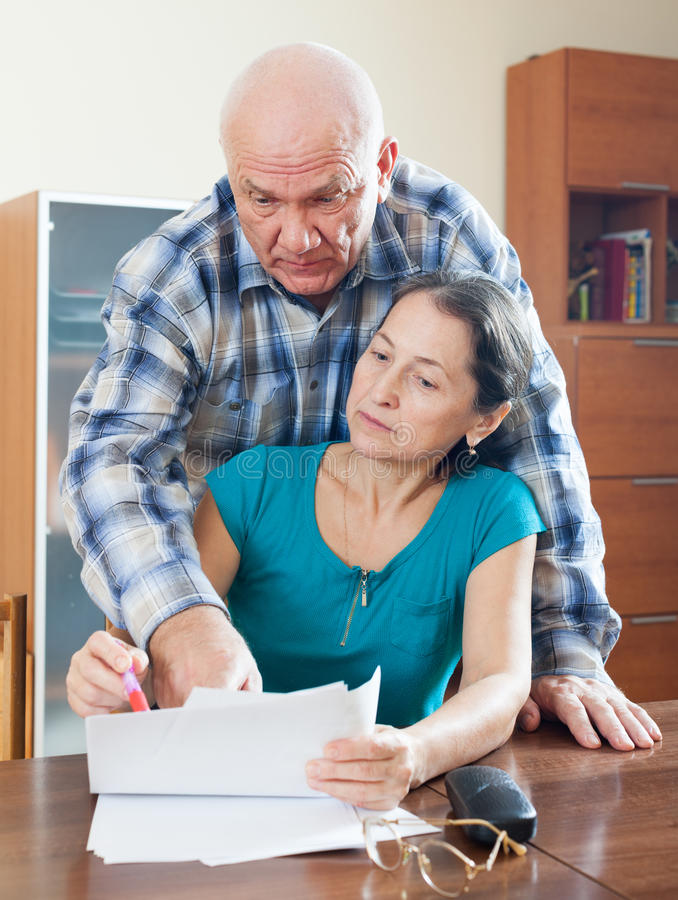 Mature woman fills documents, man helps her stock photography
