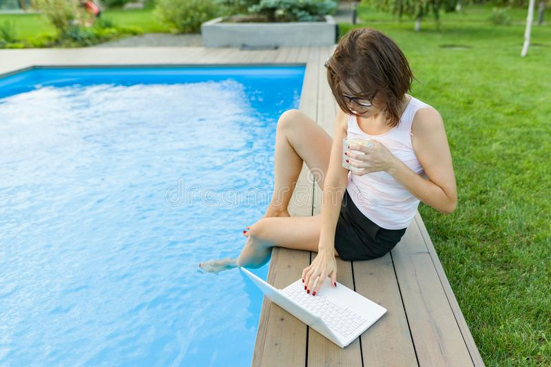 Mature woman freelancer uses a laptop sitting by the pool. Middle-aged woman blogger on a background of nature, yard, home pool is stock image