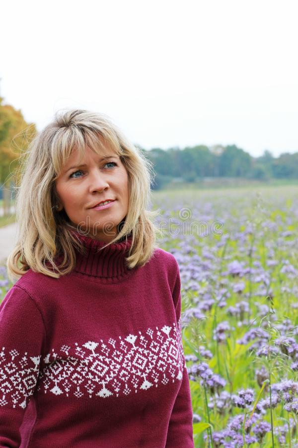 Mature woman in front of a lilac flower field stock images
