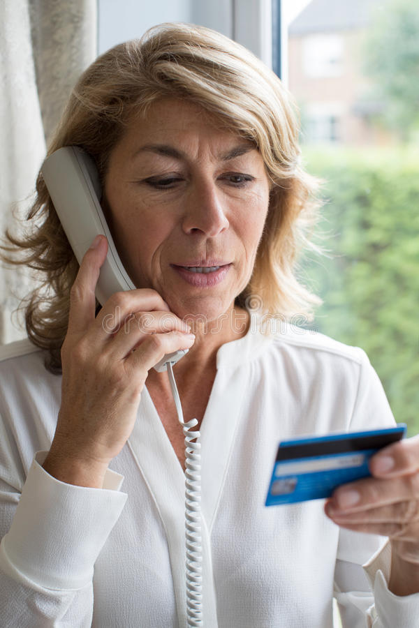 Mature Woman Giving Credit Card Details On The Phone. Mature Woman Gives Credit Card Details On The Phone royalty free stock photo