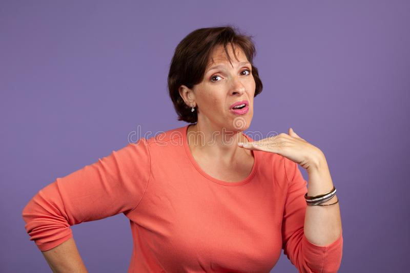 Mature woman giving cut off sign. Mature woman in an orange shirt on purple background giving the cutoff sign. Stop talking argument concept stock photos