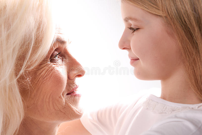 Mature woman glancing at her grandchild. Small girl is looking at happy old lady. They are hugging stock photos
